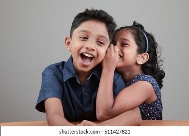 Little girl tells a secret to the boy