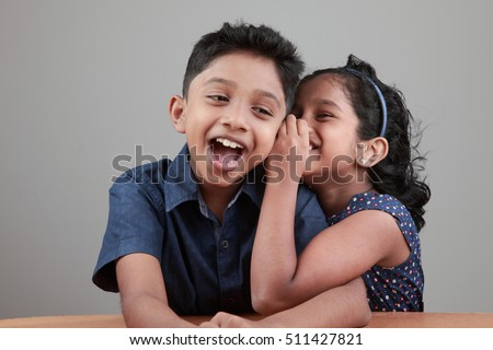 Little girl tells a secret to the boy