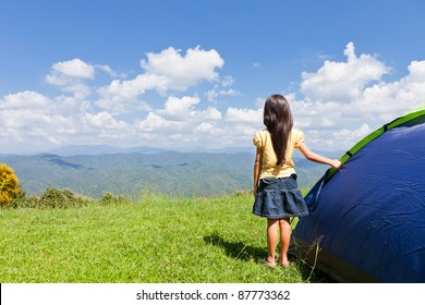 Little girl with tent on mountain