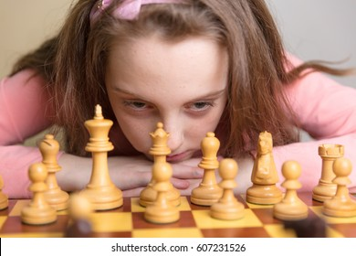 Little girl thinking about the first move while playing chess.