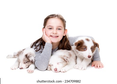 little girl with three border collie puppies in front of a white background