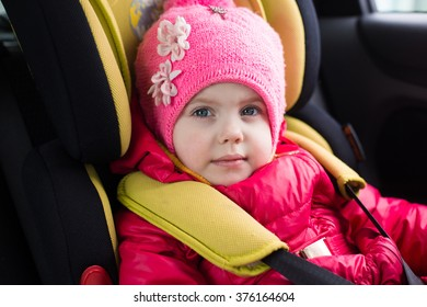 a little girl of three years in winter in a red jacket and a pink hat sitting in a car in a child car seat is going on a journey, and strapped is secure, smiling and builds funny faces