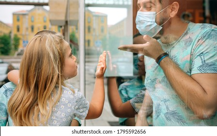 Little girl throwing a kiss through the glass to her father who is working with mask