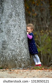 """Little girl is in """"time out"""" against a tree.  She is not happy and is frowning and whining.  She has a blue dress on and grey leggings."""