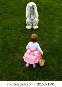 Little girl toddler suddenly meets the easter bunny while egg hunt - wonder