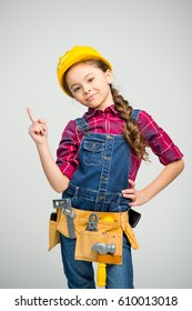 Little girl in tool belt and hard hat pointing up and smiling at camera  isolated on grey