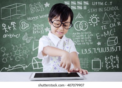 Little girl touching a digital tablet screen on the tablet in the classroom at school