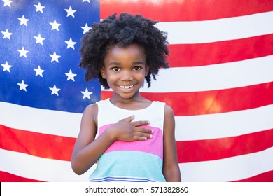 A little girl is touching her heart front of american flag