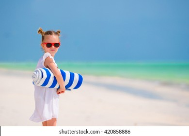 Little girl with towels on white beach vacation