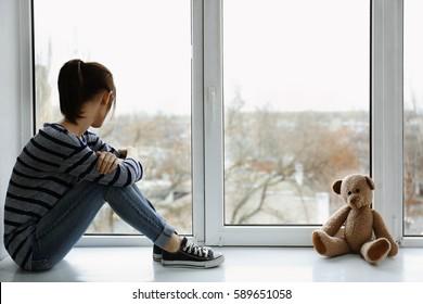 Little girl with toy bear on windowsill