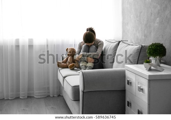 Little girl with toy bear on sofa in room