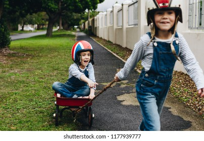 Little girl in a toy cart being pulled by her twin sister outside on road. Identical twins playing outdoors with a trolley.