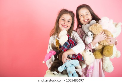Little girl with toy. Two beautiful happy girls standing and embracing plushs toy in children room. Tenderness and beauty concept. Girls holds heap of teddy bears. Girl hugging teddybears, childhood.