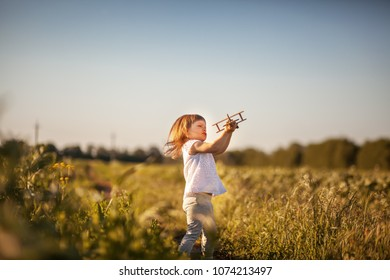 Little girl with toy wooden airplane in summer field