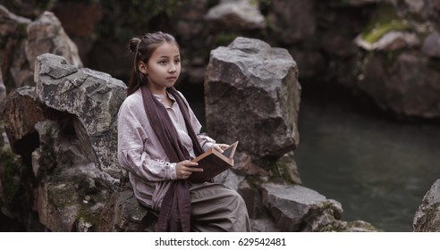 little girl in traditional Chinese clothes on the shore of the pond