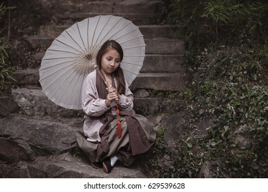 little girl in traditional clothes with Chinese umbrella