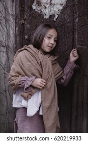 little girl in traditional clothes knocking at an old wooden door