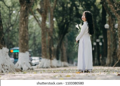 little girl in traditional costume Vietnam stood on the road with beautiful trees at sunset in Hanoi, Vietnam.
