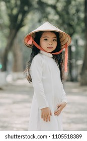 little girl in traditional costume Vietnam stood on the road with beautiful trees at sunset in Hanoi, Vietnam