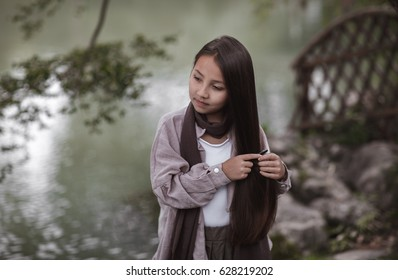 little girl in traditional dress combs her long hair at the lake