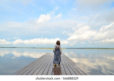 Little girl in the traditional russian dress (sarafan)  alone goes alonge  a wooden pier. View of the beautiful calm lake and clouds reflexion.
