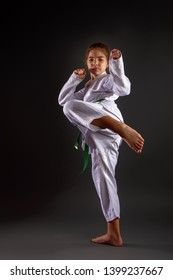A little girl in a traditional white kimono for karate and a green belt performs training exercises against a dark background.