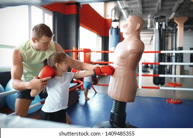 Little girl training with coach and dummy in boxing ring