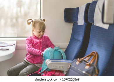 Little girl travel  by train. Kid sitting in comfortable chair and looking in backpack. Things to take with on railroad trip with children concept