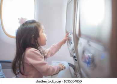 A little girl traveling by an airplane. Child sitting by aircraft window and using a digital tablet PTV during the flight.