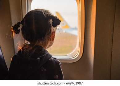 Little girl traveling by the airplane. Child sitting by aircraft
