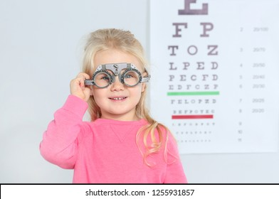 Little girl with trial frame near eye chart in hospital, space for text. Visiting children's doctor