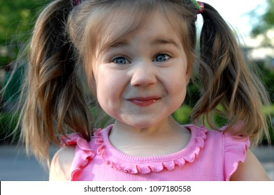Little girl tries to hold in her giggles as she puts her face into a mirthful smirk.  She has pigtails and a pink shirt.