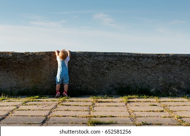 The little girl tries to see what's behind the wall.
