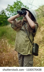 a little girl in a tropical khaki uniform and a cork with binoculars looking for adventures in nature