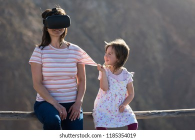 Little girl try to attract attention of her mother wearing virtual reality glasses