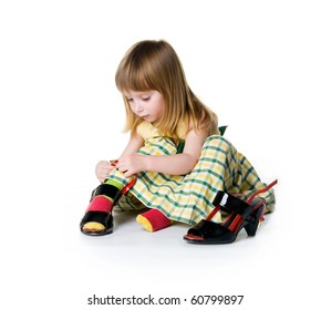 Little girl try on big shoes. Isolated on white background
