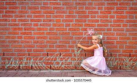 a little girl try to take a painted flower from a wall