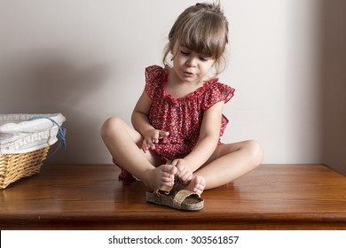 Little girl trying to put on her shoes. Indoor portrait with blank space to put your own text