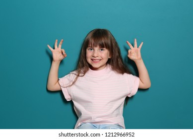Little girl in t-shirt showing OK gesture on color background