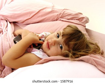 Little girl tucked into bed, holding a book
