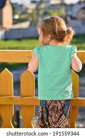 Little girl in turquoise shirt waiting for someone on a balcony at sunset