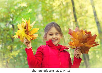 little girl with two bouquets of yellow maple leaves