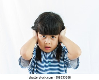 little girl with two braids is isolated on white background. Girl looking at camera and discontentedly closing her ears with hands