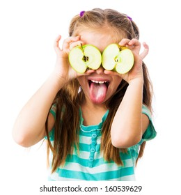 little girl with two halves of an apple near her eyes shows tongue isolated on white background