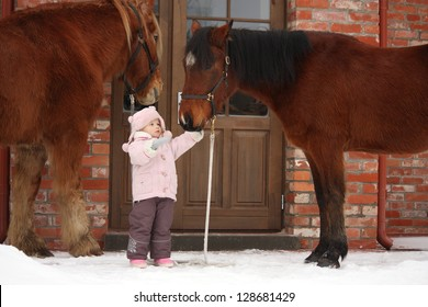 Little girl and two horses standing near the cottage door in winter