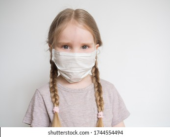 Little girl with two pigtails in medical mask. Portrait of girl standing on white background. Sad child.