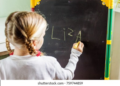little girl with two pigtails is  writing her name with chalk on a blackboard, with copy space