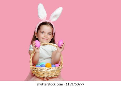 Little girl with two pink Easter eggs in her hands against pink background