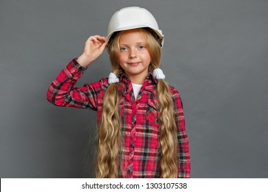 Little girl with two ponytails wearing helmet studio standing isolated on grey wall looking camera smiling confident