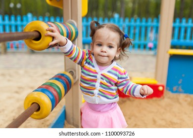 a little girl with two tails is dressed in a striped colorful jacket is playing in the sandbox on the playground Summer family leisure concept